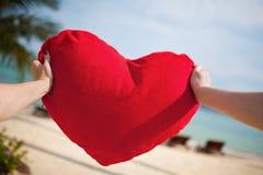 Pillow heart. Women's hands holding the pillow heart on beach background stock photos