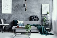 Free Pillow On Black Metal Chair Next To Grey Sofa With Pillow In Dark Living Room Interior With Maps On Empty Concrete Wall Stock Images - 162175184