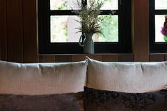 Pillow, sofa and flower beside window Stock Photo