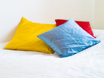 Pillows on Bed. Three colorfuls pillows on a white bed Stock Images