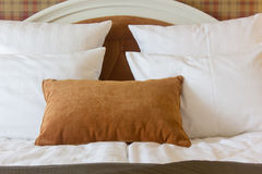 Pillows on bed in hotel room. White and brown one. Royalty Free Stock Images
