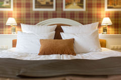 Pillows on bed in hotel room. White and brown one. Stock Photos