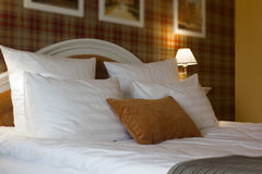 Pillows on bed in hotel room. White and brown one. Stock Photography