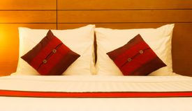 Pillows in bed at night. Red pillows in bed in bedroom at night Royalty Free Stock Photo