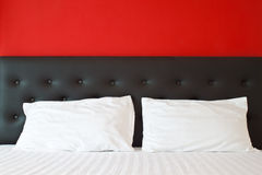 Pillows and  on bed in red bedroom. Clean white pillows and  on bed in red bedroom Royalty Free Stock Images