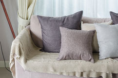 Pillows and blanket on earth tone sofa in Stock Image