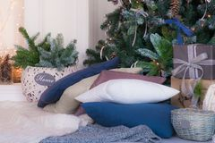 Pillows and blanket beside the fireplace near the Christmas tree. Place with pillows and blanket beside the fireplace near the Christmas tree and gifts Stock Image