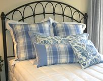 Pillows in Blue. Blue pillows on wrought iron bed royalty free stock photography