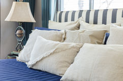 Pillows on blue bed with lamp Stock Images