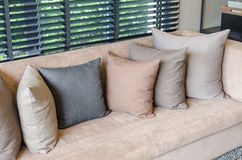 Pillows on brown sofa Stock Images