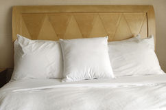 Pillows of Comfort. Group of several white pillows on a bed with headboard Stock Photography