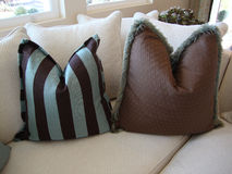 Pillows on a Couch/Sofa. Beautiful brown and blue pillows one striped and one with dots and fringe on a cream colored sofa or couch Royalty Free Stock Photo