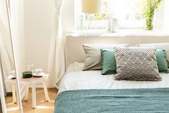 Pillows and green sheets on bed in bedroom interior with white t royalty free stock photography