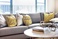 Pillows on the grey sofa beside a window and sunlight Stock Image
