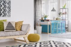 Yellow pouf in spacious room. Pillows on grey sofa and yellow pouf in spacious living room with stools at blue table and white bucket royalty free stock image