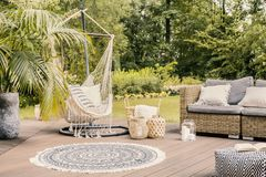 Pillows on hammock on terrace with round rug and rattan sofa in. The garden. Real photo stock photos