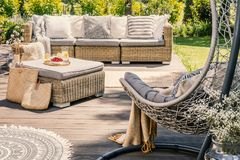 Pillows on rattan couch and table on patio with hanging chair du. Ring summer. Real photo stock image