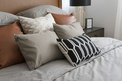 Pillows setting on bed with brown leather headboard Royalty Free Stock Photography