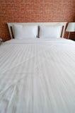Pillows Sheets and Brick Wallpaper Stock Photo