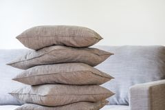 Pillows stacked in a pile. Big gray sofa in the background stock images