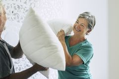 Pillows war at home for caucasian couple of playful adult senior man and woman play in the bedroom at the morning. hapiness and. Pillows war at home for stock photos