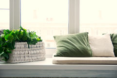 Pillows on the windowsill and plastic window. Wicker basket with Stock Image