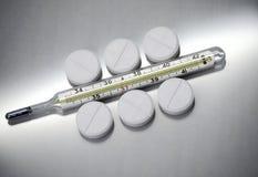 Pillren ligger bredvid den medicinska termometern royaltyfri foto
