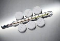 Pillren ligger bredvid den medicinska termometern royaltyfri bild