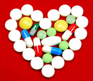 Pills. Heart made by various pills on red background Royalty Free Stock Photos