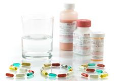 Pills. Glass of water, medicine bottles, pills forming the word SOS stock photography