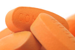 Pills. On Spoon. White background. Orange Color royalty free stock image