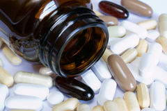 Pills. Photo of brown glass pill bottle with a variety of pills and capsules spread around royalty free stock images