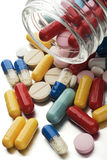 Pills. Multicolored pills out of the bottle on white royalty free stock photo