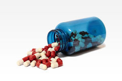 The blue bottle of pills. Open and dumped blue bottle of pills Royalty Free Stock Photos