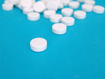Pills. White pills, aspirin, isolated on blue background Stock Image