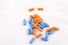Pills. Set of blue and orange pills, white background Royalty Free Stock Images