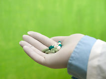 Pills. In doctors hand, green wall Stock Photography