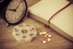 Daily pills and alarm clock with diary Royalty Free Stock Image
