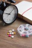 Daily pills and alarm clock with diary Stock Photos