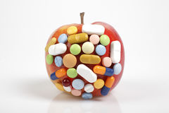 Pills on apple on white background symbolizing chemical contamination of food Royalty Free Stock Image