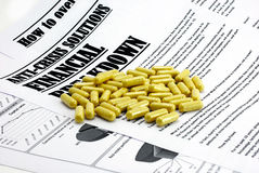 Pills upon article about financial crisis isolated Royalty Free Stock Images