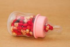 Pills in baby bottle Stock Image