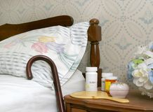 Pills on a bedside table. Medicine bottles and a cane against a bed for an elderly person royalty free stock images