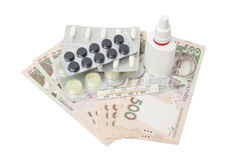 Pills in a blister pack, thermometer and nasal spray. With ukrainian money isolated on a white background Royalty Free Stock Photo