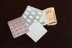 Pills in blister packaging and 50 Euro banknote. On dark background royalty free stock photography