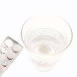 Pills in blister with water. A blister package holding three pills with a glass of water, isolated on white stock images