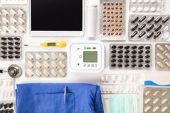 Pills By Blood Pressure Machine With Digital Tablet And Scrubs. Directly above shot of colorful pills in blister packs by blood pressure machine with digital royalty free stock photo