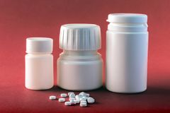Pills Boats White With White Tablets Of Different Types Isolated On Red Backgrou. Conceptual image Stock Images