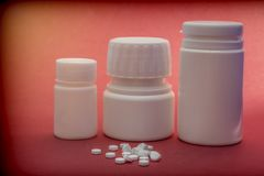 Pills Boats White With White Tablets Of Different Types Isolated On Red Backgrou. Conceptual image Royalty Free Stock Photography
