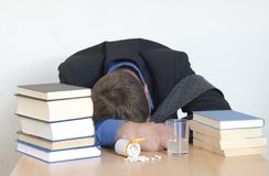 Pills and books. Businessman passed out in the office. Sleeping pills at the desk Royalty Free Stock Photography